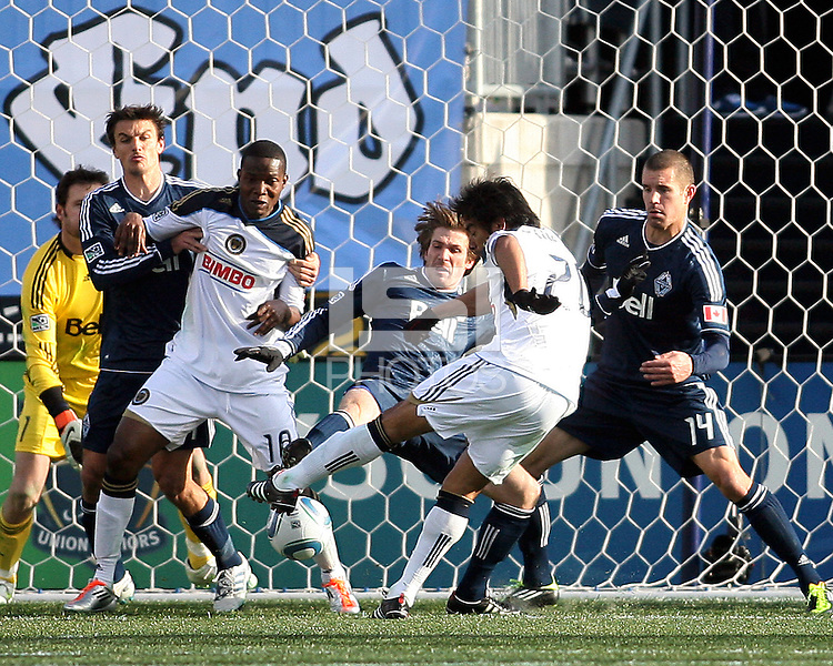 Carlos Ruiz#20 of the Philadelphia Union blasts a shot at Alain Rochat#4 and Greg Janicki#14 of the Vancouver Whitecaps during an MLS match at PPL Park in Chester, PA. on March 26 2011. Union won 1-0.