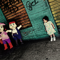 A little Salvadorean girl looks at the paper dolls sold for the child birthday festivities in San Salvador, El Salvador, 22 December 2013.