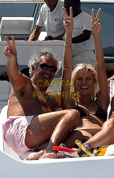 Flavio Briatore & Heidi Klum .On holiday, Costa Smeralda, Sardinia , Italy..July 11th, 2003.full length couple vacation holiday sun sunglasses shades brown bikini hands arms in air braid plait hands v peace sign pink shorts .CAP/PPG.©People Picture/Capital Pictures
