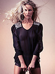 Fashion photo of young beautiful woman with flying long blond hair wearing black see-through top on beige background