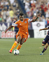 Houston Dynamo midfielder Giles Barnes (23) on the attack.  In a Major League Soccer (MLS) match, Houston Dynamo (orange) defeated the New England Revolution (blue), 2-1, at Gillette Stadium on July 13, 2013.