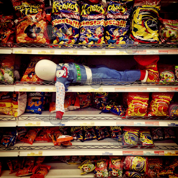 A doll rests among the packets of snacks on the selves of Megamaxi, a super store in the Scala Mall.