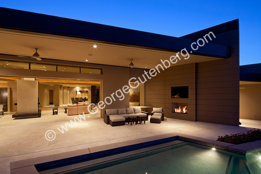 Evening view of patio areas of outdoor living spaces of home to opens to inside
