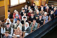 Nederland Broek op Langedijk 2015.  Nationale Folkloredag, met veel mensen in Nederlandse  klederdracht, bij Museum de BroekerVeiling. De Broekerveiling is de oudste doorvaarveiling ter wereld. Mensen in klederdracht zitten in de Afmijnzaal