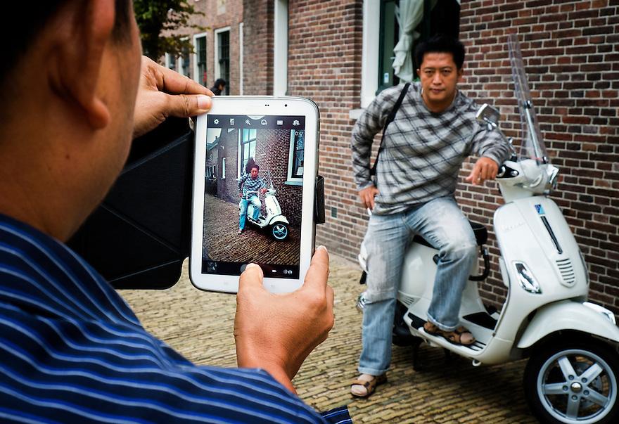 Nederland, Zaanstad, 8 sept  2013<br /> Zaanse Schans. Chinese toeristen maken foto met tablet van man stoer leunend op scooter.<br /> Chinese tourists make photos with a white scooter. <br /> Foto(c): Michiel Wijnbergh