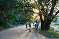 Runners and bikers exercise to maintain a healthy lifestyle on the beautiful Lady Bird Lake Hike and Bike Trail in downtown Austin on a beautiful summer day - stock image.