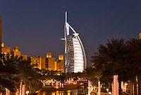 Dubai.  Evening view over Madinat Jumeirah and Mina a?Salam Hotel of Burj al Arab Hotel, architect W.S. Atkins, an icon of Dubai built in the shape of the sail of a dhow, stands on an island off Jumeirah Beach.  .