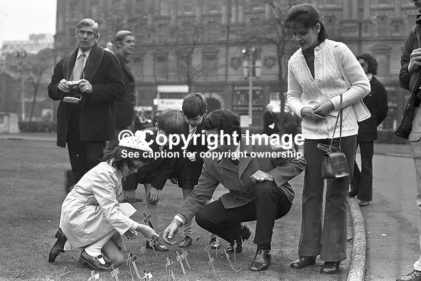 The family of 18 month old Angela Gallagher, like hundreds of others, gather in the grounds of Belfast City Hall, N Ireland, UK, to plant crosses at an event to remember the innocent victims killed during the N Ireland Troubles. It took place on Sunday 5 November 1973. The picture includes parents, Peter and Irene Gallagher, and 8 year old Paula, in whose arms her baby sister died.  Angela died on 3 September from a ricocheting bullet during a Provisional IRA sniper attack on a Scots Guards patrol. The incident happened close to the home of Angela's grandmother in Iveagh Street, West Belfast. 197211050683a..Copyright Image from Victor Patterson, 54 Dorchester Park, Belfast, UK, BT9 6RJ..Tel: +44 28 9066 1296.Mob: +44 7802 353836.Voicemail +44 20 8816 7153.Skype: victorpattersonbelfast.Email: victorpatterson@mac.com.Email: victorpatterson@ireland.com (back-up)..IMPORTANT: If you wish to use this image or any other of my images please go to www.victorpatterson.com and click on the Terms & Conditions. Then contact me by email or phone with the reference number(s) of the image(s) concerned.