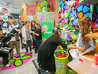 "An assistant adjusts the outfit of Latin female singer Leslie Grace at an appearance at the Happy Family Laundromat in the Bronx borough of New York on Friday, May 16, 2014 during a promotional event for Procter & Gamble's Gain ""Flings"" detergent pods. Procter & Gamble redecorated the laundry in a 60's ""flower power"" motif with the help of students working with the Portraits of Hope non-profit. Portraits of Hope works with children in hospitals and previously used the same motif to cover NYC taxis. Leslie Grace (Martinez) is a19 year old bilingual Latin recording artist.  P&G has decorated six laundromats throughout the city in this fashion. (© Richard B. Levine)"