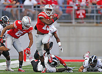 Ohio State Buckeyes running back Ezekiel Elliott (15) gets away from Cincinnati defenders during the first quarter of Saturday's NCAA Division I football game at Ohio Stadium in Columbus on September 27, 2014. (Columbus Dispatch photo by Jonathan Quilter)