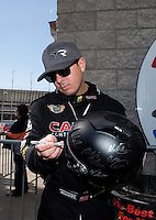 Mar 30, 2014; Las Vegas, NV, USA; NHRA top fuel driver Steve Torrence autographs a helmet during the Summitracing.com Nationals at The Strip at Las Vegas Motor Speedway. Mandatory Credit: Mark J. Rebilas-