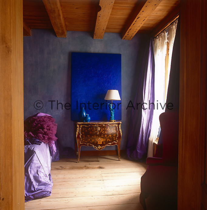 A view into a blue bedroom with a beamed ceiling and wood floor. A modern canvas in vibrant blue contrasts with an antique ormolu commode. The curtains and bed cover are in a silk purple.
