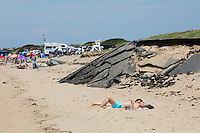 Mehmet Mat (front) and Banu Mat, both visiting Turkey, relax on the beach during their vacation at Herring Cove Beach in the Cape Cod National Seashore outside of Provincetown, Mass., USA, on Fri., July 1, 2016. Portions of the parking lot have been closed after land eroded during storms earlier this year. Also visible here, a part of a bike and walking path close the beach has collapsed.