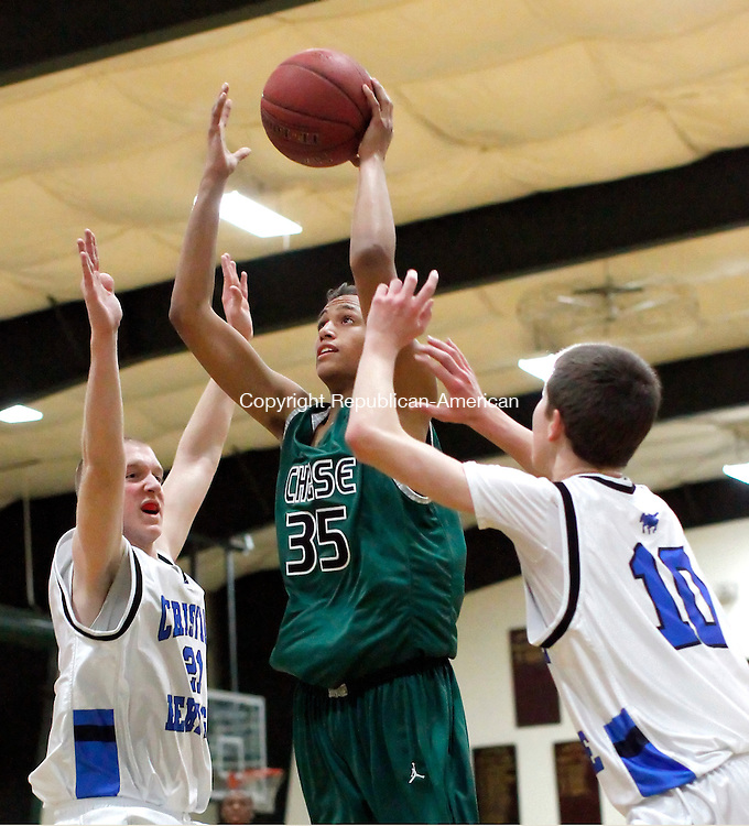 Waterbury, CT-02 December 2011-120211CM06-  Chase Collegiate's Matt McClain goes to the hoop over Christian Heritage's Sean Kasouff (left) and Jacob Clark  during their matchup in Waterbury Friday night.  Chase lost their season opener, 76-50.   Christopher Massa Republican-American
