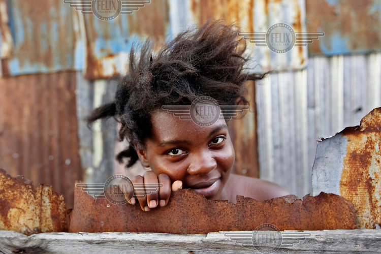 A woman peers out from rusted corrugated metal in the Cite Soleil slum.