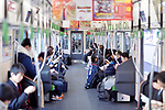 Commuting people sitting inside JR train in Kyoto, Japan 2017