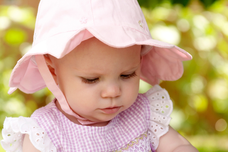 Baby girl in sun hat on summer day