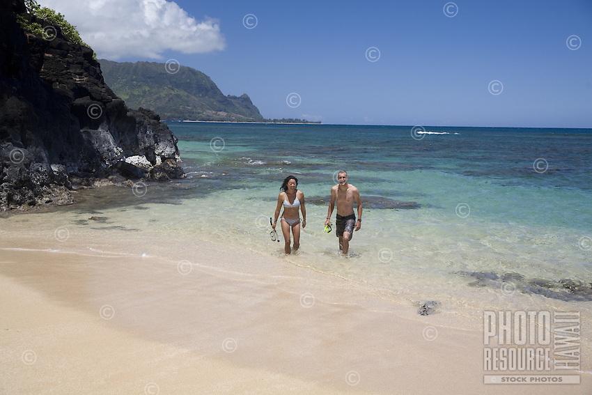 Smiling couple walking out of the clear blue water with their snorkeling gear at Hideaways Beach on Kauai