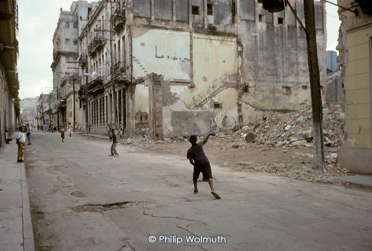 Young boys play baseball in a crumbling street in Central Havana (Havana Centro). Derelict houses are demolished when they become unsafe and repair is too expensive.