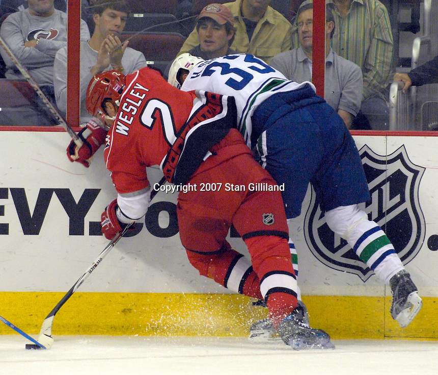 Carolina Hurricanes Glen Wesley (2) and the Vancouver Canucks' Henrik Sedin (33) collide battling for a puck during their game Monday, Oct. 22, 2007 in Raleigh, NC. The Hurricanes won 3-1.