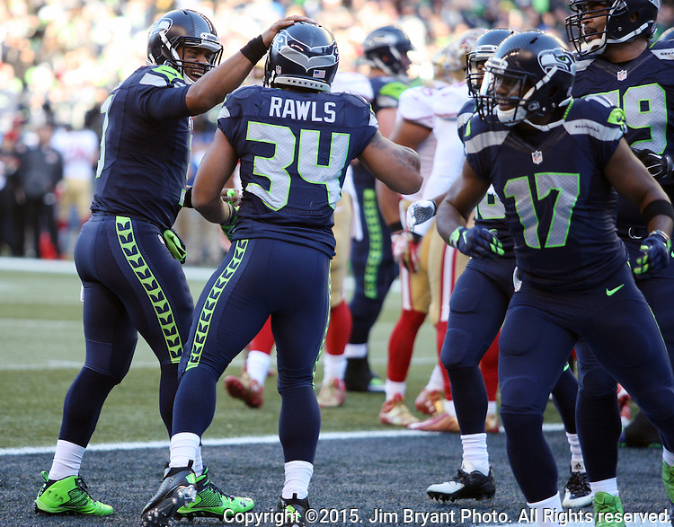 Seattle Seahawks quarterback Russell Wilson (3) celebrates running back Thomas Rawls'  (34) two-yard touchdown against the San Francisco 49ers at CenturyLink Field in Seattle, Washington on November 22, 2015.  The Seahawks beat the 49ers 29-13.   ©2015. Jim Bryant Photo. All RIghts Reserved.