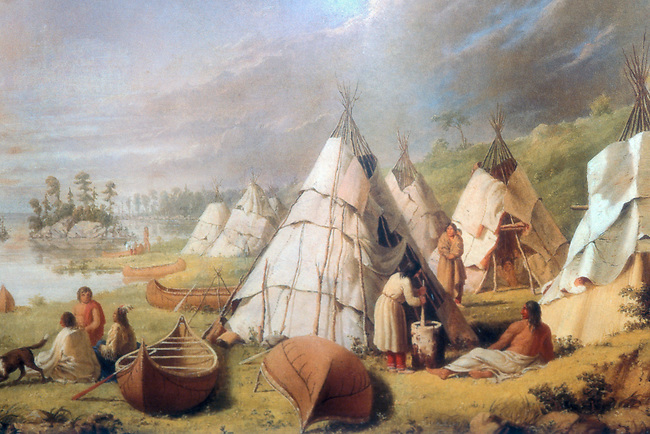 Historic painting of a Chippewa (Ojibway) encampment showing daily village life with dwellings covered with sheets of bark, a woman grinding corn using a large log mortar and pestle and sitting along the lake bank are birch bark canoes used for transportation.