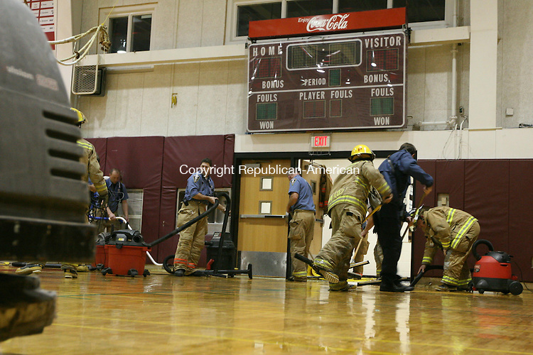 TORRINGTON, CT - 25 October, 2008 - 102508MO06 - Torrington firefighters and school staff scramble to save the hardwood gym floor at Torrington High School Saturday morning after a sprinkler head in the hallway outside was broken, flooding first-floor hallways and the gym with 1,000 gallons water, or more. A two-alarm response by city firefighters backed up by Torringford volunteers may or may not have succeeded in saving the floor from significant damage. Jim Moore Republican-American.