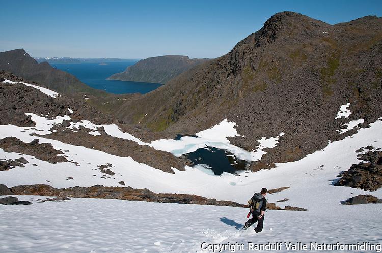 To personer på vei ned snøfelt mot Engerdalvatnet på Seiland.  ----- Two people decending a snow field on Seiland.