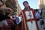 An acolyte gives the spectators cards with pictures of his brotherhood images during a Holy Week procession, Seville, Spain
