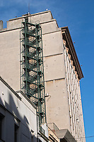 A tall modern building in the financial district with a fire escape ladder on the side against a blue sky. Montevideo, Uruguay, South America