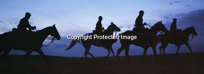 Members of the Commanding General's Mounted Color Guard out of Fort Riley, Kansas head out at dusk to take part in the Major Howze team competition at the 2008 Annual Bivouac and National Cavalry Competition. The Howze military exercise trains soldiers in night time navigation and battle. Michael Smith/staff