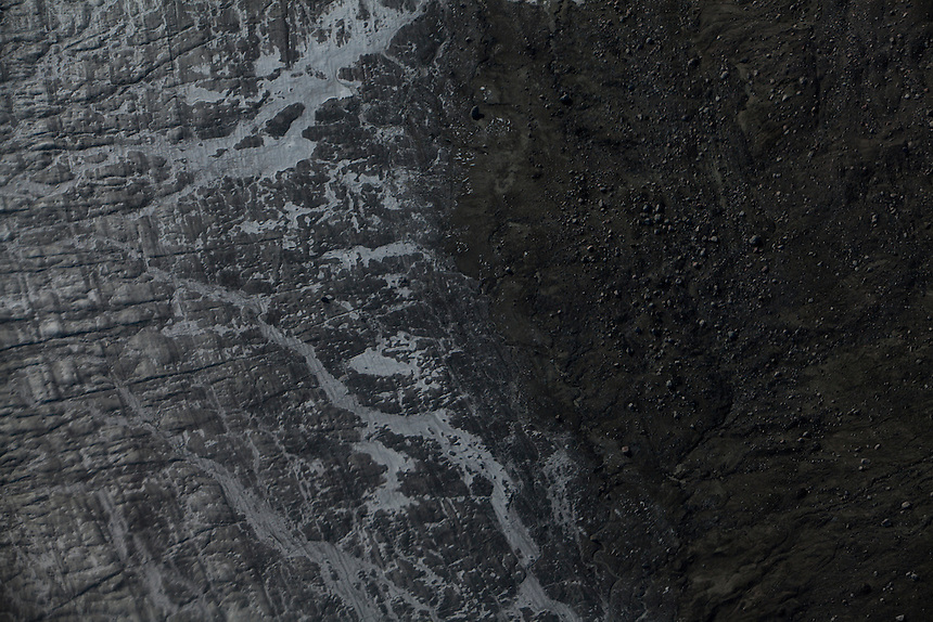 The edge of the ice cap, streams of melt water and a glacial moraine of dust and rocks, viewed from a helicopter, West Greenland, August 2011. Photo: Ed Giles.