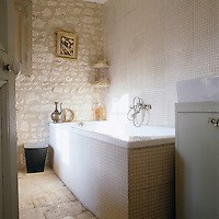 Mosaic tiles in a neutral shade have been used in the bathroom and compliment the original rough stone wall of the property