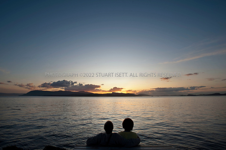 8/25/2009--Pender Island, British Columbia, Canada..Larry and Linda Wenezenki from Vancouver Island, BC, enjoy sunset views of the Gulf Islands from Thieves Bay on Pender Island...©2009 Stuart Isett. All rights reserved.