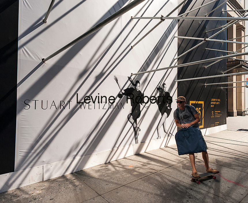 """A skateboarder swings by the construction shed for the new """"Coach House"""" on Fifth Avenue in New York on Monday, August 29, 2016. Coach announced it will open a ritzy store on expensive Fifth Avenue in an effort the raise the luxury status of their brand. The space will be 23,400 square feet with the Weitzman store adjacent on the avenue where rents can run $4000 a square foot. The store is scheduled to open in Fall 2016. (© Richard B. Levine)"""