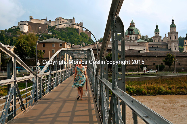 Walking across the Mozart Pedestrian Bridge over the Salzach River, towards Salzburg Cathedral and the Hohensalzburg Fortress at sunset