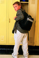 Elementary school student at locker with backpack