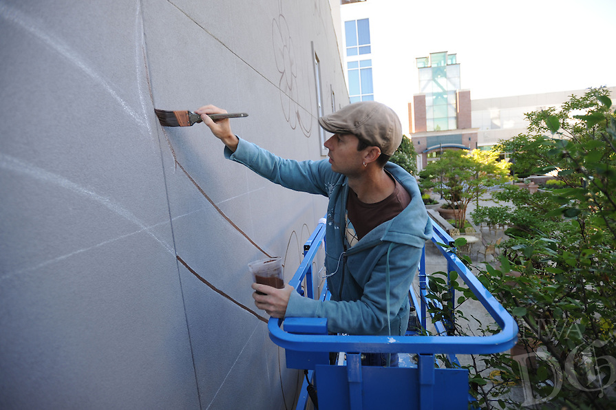 NWA Democrat-Gazette/ANDY SHUPE<br /> Jason Jones, an artist based in Fayetteville, paints Thursday, Aug. 20, 2015, while working on a mural on the east wall in the plaza outside the Fayetteville Town Center. The Fayetteville Advertising and Promotion Commission in May agreed to pay Jason Jones $11,250 to paint the mural which will feature a tree with a bear on a swing with the words Enjoy Local.