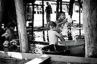 Iquitos, Peru, Jan. 11, 2007 - Two young boys bath while their mother washes clothes and their father finishes his swim, under their home in Bélen, a small poverty-stricken area built along the flats of the Amazon River. It is comprised of homes built on stilts or of floating balsa wood. During the wet season the river rises several meters causing those on stilts upstairs and all other to float. During the afternoons the temperatures can reach 100 degrees, so many do activities near or in the river, such as swimming, bathing and washing clothes or dishes.