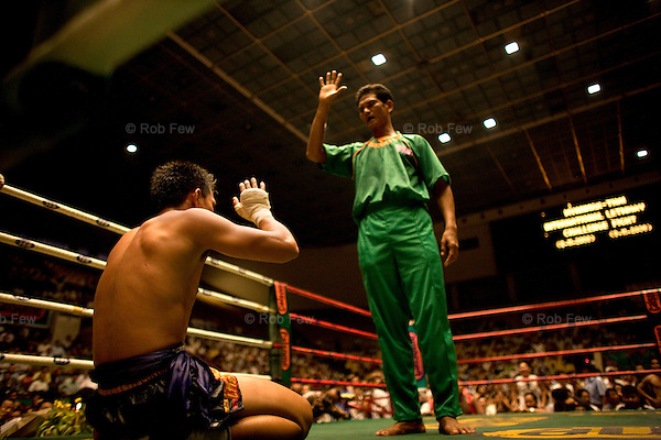 A boxer struggles to rise before his ten seconds are up.<br /> <br /> In November 2008, Yangon played host to the first ever international boxing match held in Burma. Thai boxers came for a two-day fight in Yangon's central stadium - a grueling event and a litmus test for future international sporting events in the closed-off country.