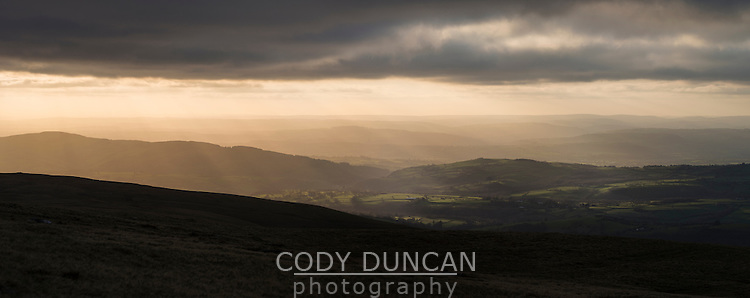 Rays of Light shine over countryside from summit of Waun Lefrith, Black Mountain, Brecon Beacons national park, Wales