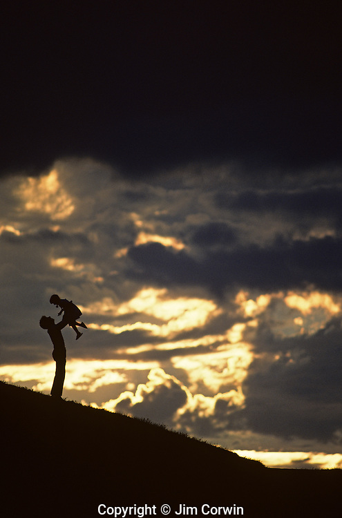 Father holding daughter above his head along hillside silhouetted.