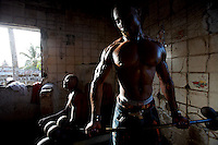Nimley, 26 years old, trains his biceps while lifting weights in his neighborhood improvised gym in Monrovia, Liberia on Tuesday  March 20 2007. .Marshall, Nimley and the other men working out are all unemployed. they spend their days at the gym to fight chronic depression..