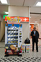 Mar. 10, 2011 - Tokyo, Japan - A businessman stands beside a vending machine stocked with Dole brand bananas inside Shibuya Station. A single banana is priced at 130 Japanese yen and a bunch of five or six is priced at 390 Japanese yen.