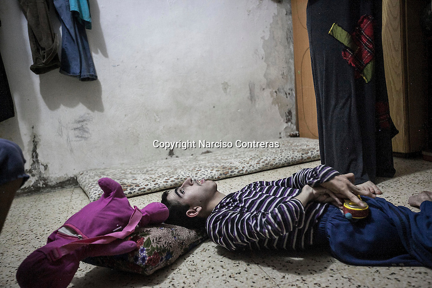 June 09, 2015 - Beirut, Lebanon: Widaad (right bottom) is standing as the brother of Jamal (not pictured), who suffers from a disability, lays on the ground at their room house in Shatila refugee camp. They are Syrian refugees from the city of Al Qusayr from where they fled four years ago when the fighting sparked out between opposition armed groups against loyalists to President Bashar Al-Assad. (Photo/Narciso Contreras)
