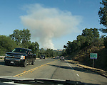 A plume of smoke rises from the Calaveras County Middle Bar wildfire and is seen from Jackson, Calif.