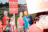 Republican presidential candidate Carly Fiorina marches in the Labor Day parade surrounded by supporters in Milford, New Hampshire. Republican candidates John Kasich, Carly Fiorina, and Lindsey Graham, and Democratic candidate Bernie Sanders marched in the parade.