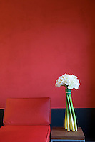 A contemporary white flower arrangement is placed on a simple wood and metal table beside a red leather chair in the lobby of the Marques de Riscal wine complex and hotel