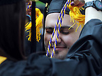 (Framingham 051913)  Tom Coughlin of Walpole, gets  his tassels bounced off his forehead by Elizabeth DeDecko of Mashpee,  Sunday prior to the commencement ceremony at Framingham State University.  (Jim Michaud Photo)