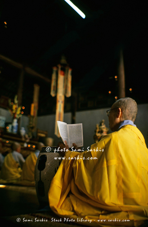 Buddhist monk reading prayers from a book inside a pagoda, Vietnam.